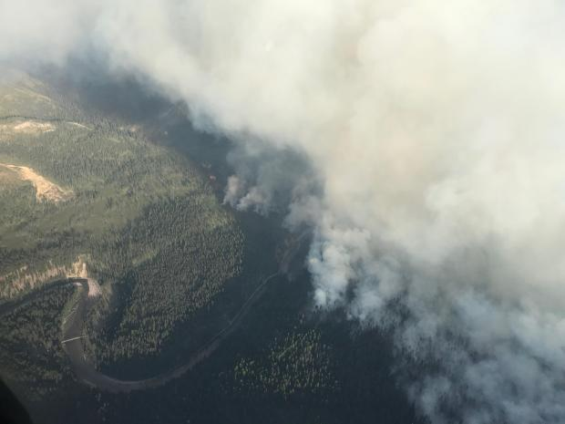 The Snow Creek Fire as seen looking southeast into the Helen Creek drainage; spot fires have established across the South Fork of the Flathead River. The Black Bear Pack Bridge can be seen in the lower left section of the photo.