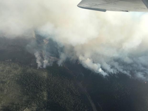 The Snow Creek Fire as seen looking south. Spot fires that have established in the mouth of the Helen Creek drainage can be seen to the east; the fire is spreading from the Snow Creek drainage towards Hungry Creek to the north.