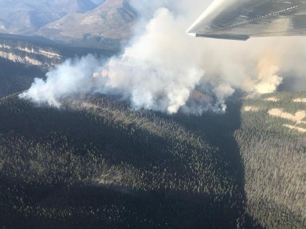 The Snow Creek Fire as seen looking northeast from the Snow Creek drainage. The fire is seen actively burning along the south facing slope and into the mouth of the Snow Creek drainage. Spot fires have established across the river.