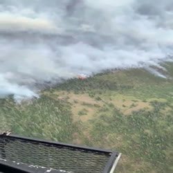 An overhead view of smoke rising from heavy timbered slope, with green timber surrounding the area with fire.