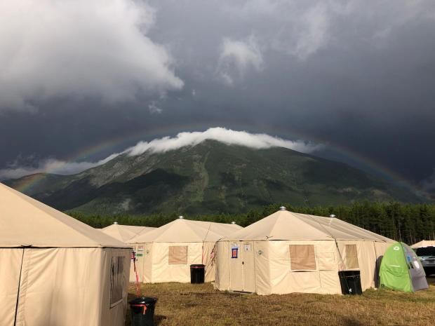 A rainbow appeared against the tree covered mountains with canvas tents in the foreground.