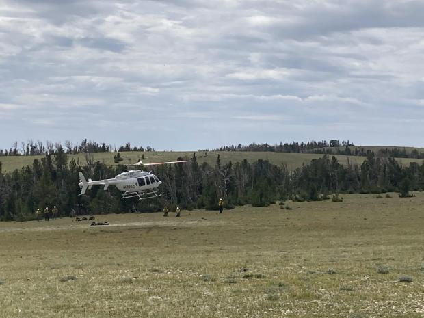 A helicopter lifts off the ground with the 6 firefighters firefighters waiting for it to clear in the background