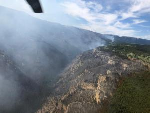 Mountainous terrain with smoke seen from helicopter