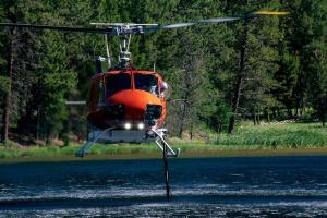 Photo illustrating a Bell 205 Type 2 helicopter equipped with belly tanks refilling out of Herrin Lake near Lincoln MT.  Photo Credit:  Roger Dey