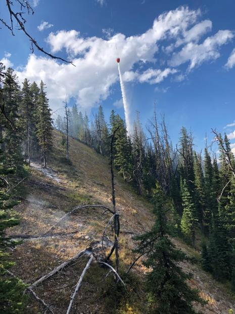 A helioopter drops water, cooling a hot spot on the Wood Lake Fire