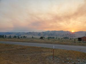 Image shows sunrise over the Woods Creek Fire, July 30, 2021