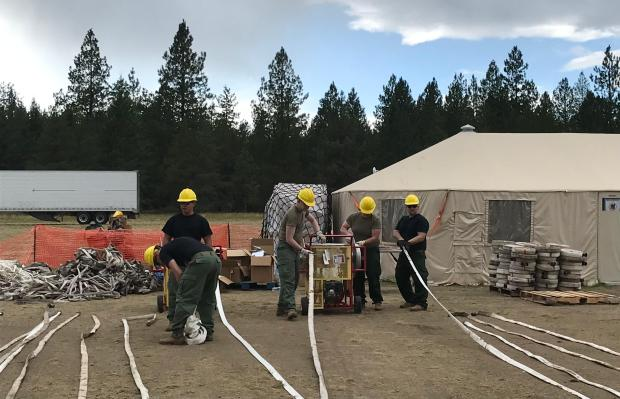 Members of the Montana Army National Guard rolling hose at camp, Aug. 23