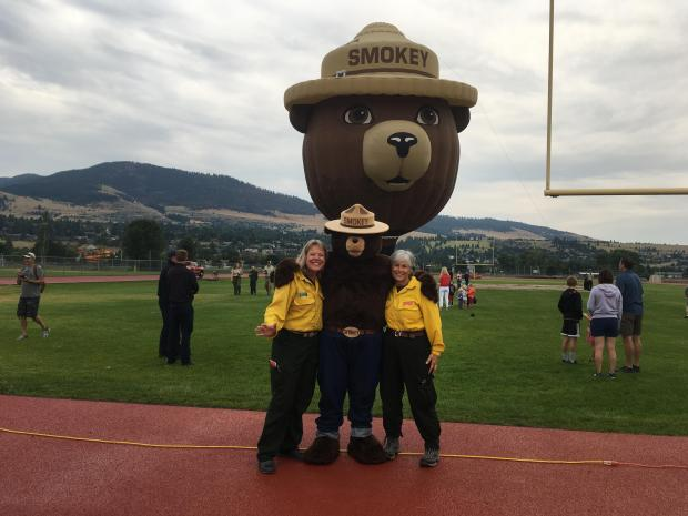 Very large hot air balloon in shape of Smokey Bear with Smokey character and two women in yellow shirts in foreground.