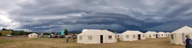 white tents with dark gray clouds in sky above them