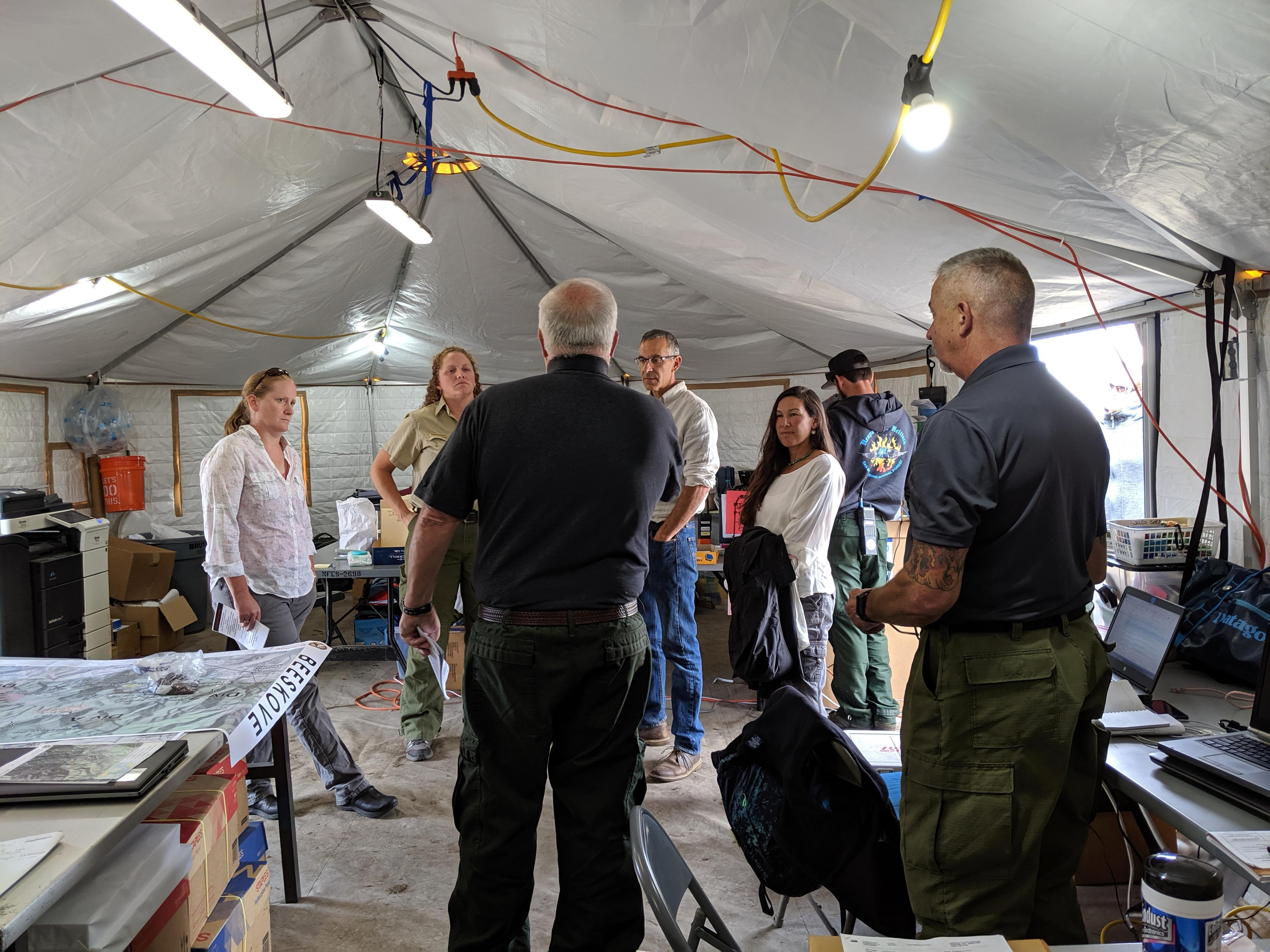 People gathered in a tent having a discussion