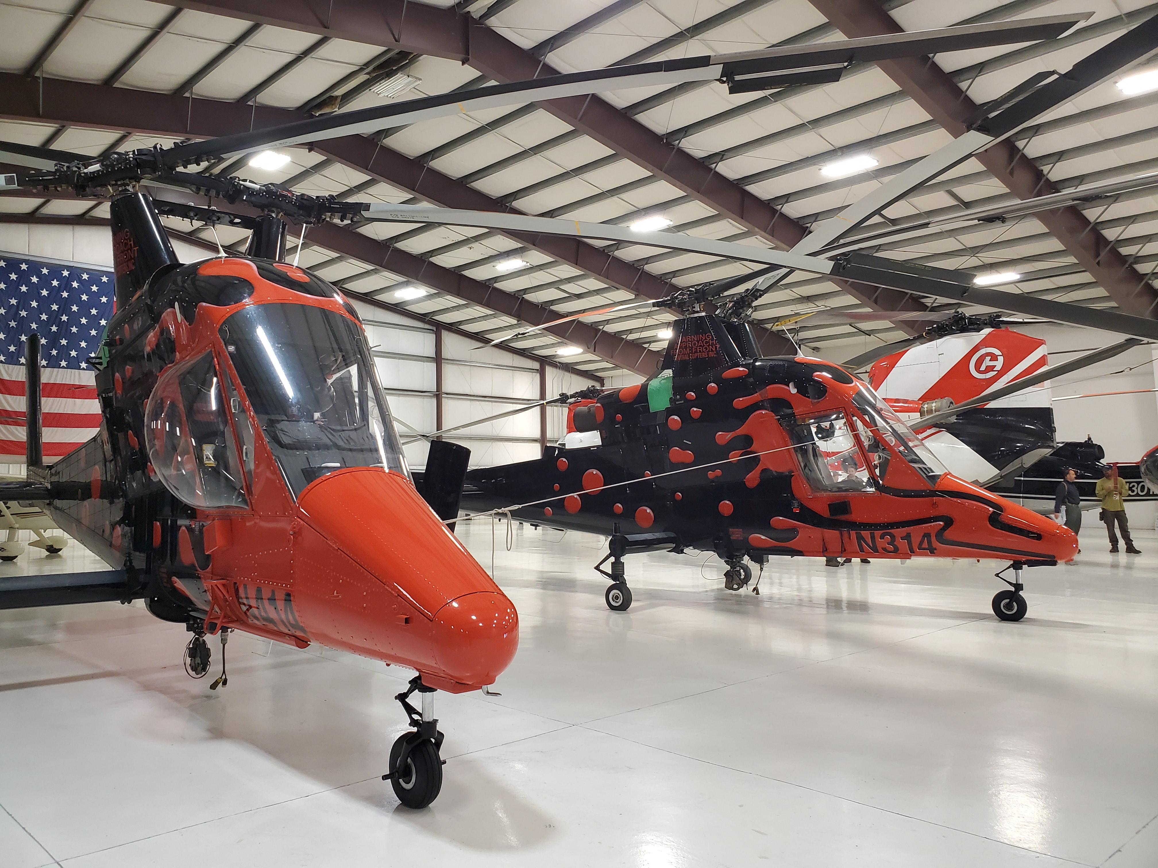 Two black and orange helicopters in a large shelter