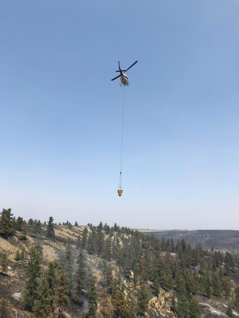 A helicopter hauls water over the Harris Fire