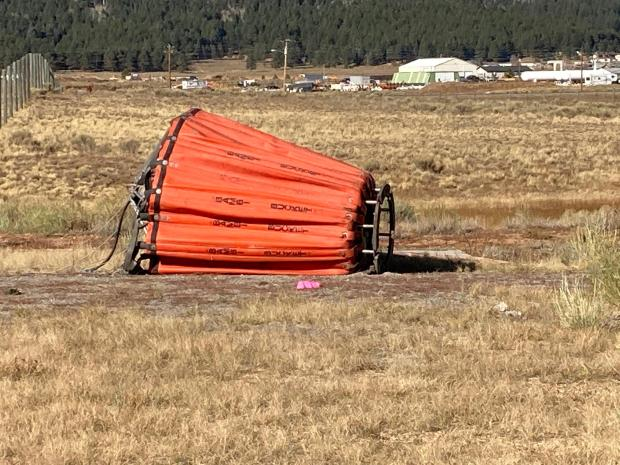 Bucket on the ground attached to the helicopter that can hold approximately 900 gallons.