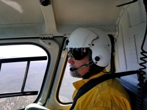 Specialists gain aerial view of the fire via helicopter flight.