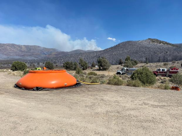 An orange tank is on the ground with a helicopter hovering nearby.
