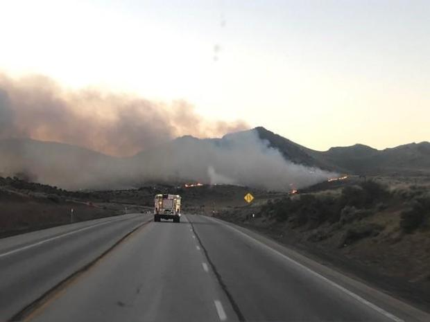 A fire engine on the highway drives towards the fire.