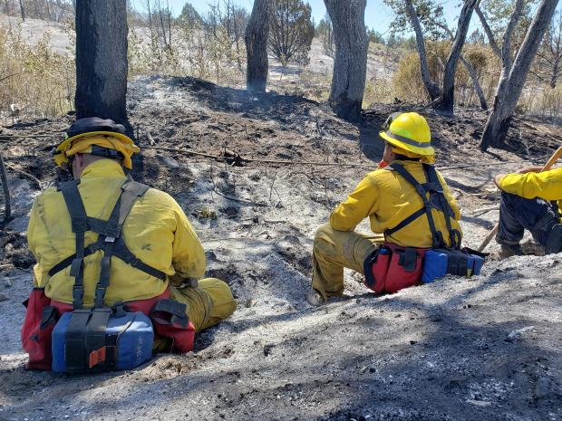 Firefighters sitting on burnt ground.
