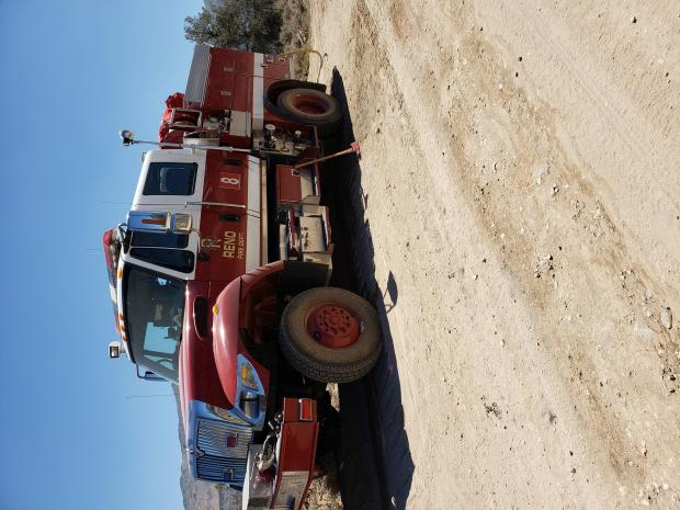 Red fire engine parked on dirt road.