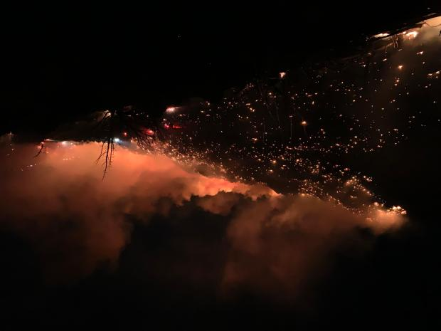 Wildfire burning at night with flames and smoke in the dark.