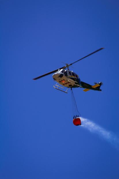 Helicopter flying in sky with water bucket.