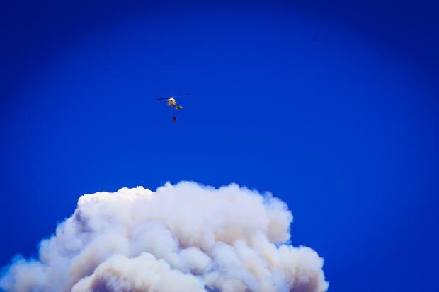 Helicopter in distance near wildfire smoke plume.
