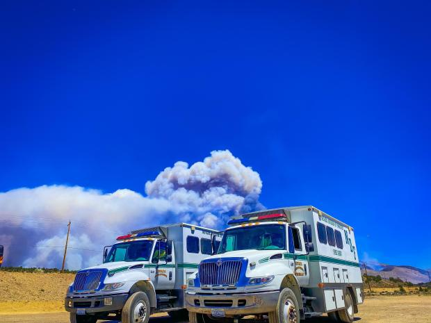 Two engines in front of wildfire smoke plume.