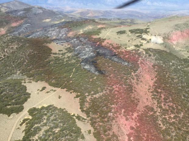 Red retardant line over forested area.