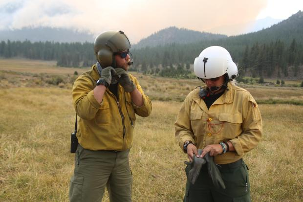 Two firefighters standing in a meadow with flight helmets on.