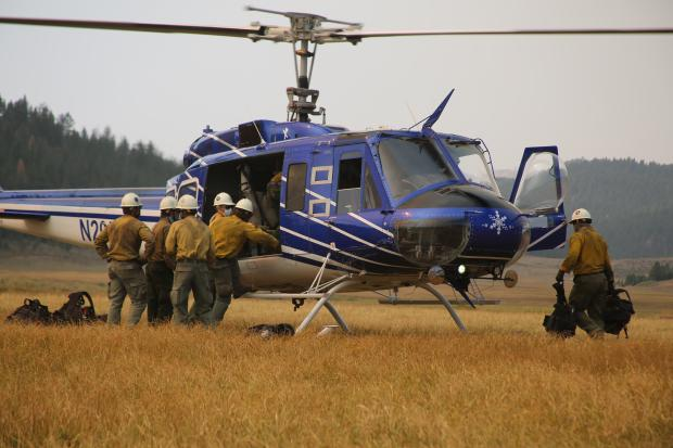 Firefighters loading onto a helicopter in a meadow.