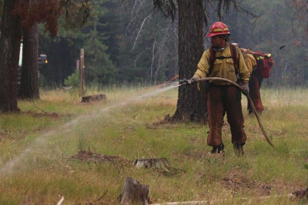 A firefighter sprays down a suspected spot fire with a hose.