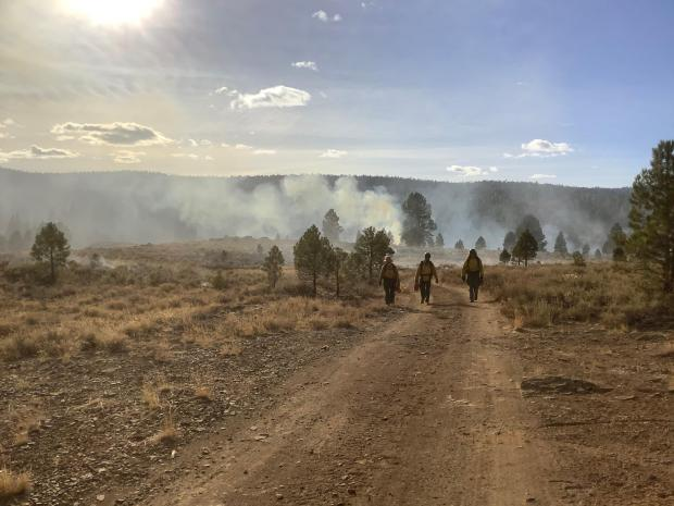 Three figher fighters walking up a dirt road with smoke along the horizon in the background.