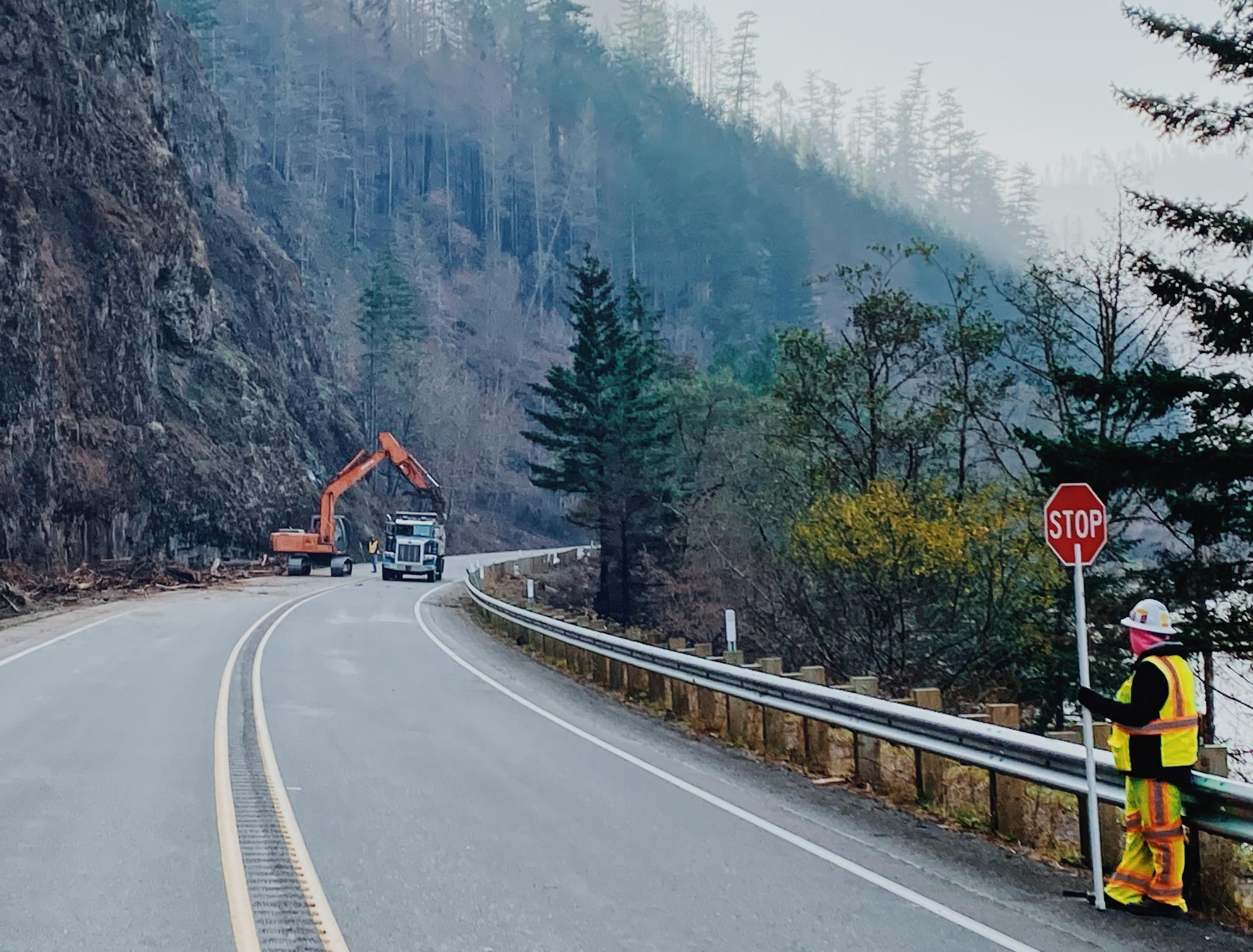 A road guard halts traffic as an excavtor removes debris that fell from rock faces above Highway 224.