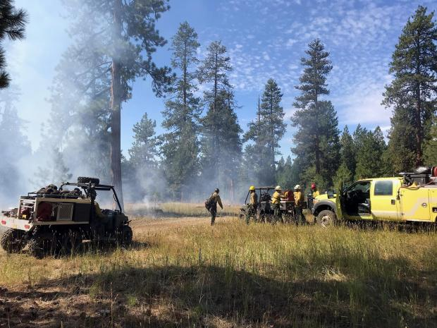 Firefighters and equipment gather along the northwest boundary of the Canyon 66 Rx burn unit following the morning 5-acre test burn.