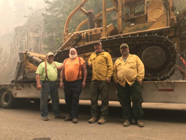 Four massive, smiling men lean against a low boy trailer loaded with heavy equipment.