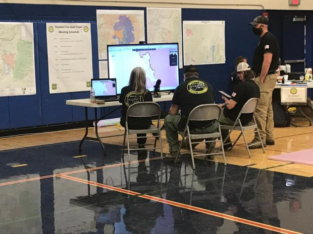 Members of the Gold Team look at a map of the Thielsen Fire on a huge monitor.
