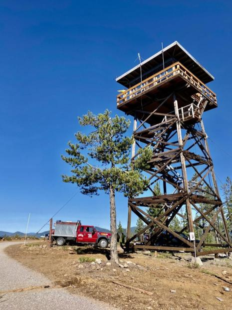 Engine crew checking Cinnamon Butte Fire Tower and  Steve Gray, Safety Officer, is at the top pointing,