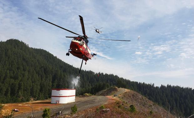 Sikorsky S-61 is dipping out of a water tank on the Chaos Fire. The aircraft can hold 500 gallons.