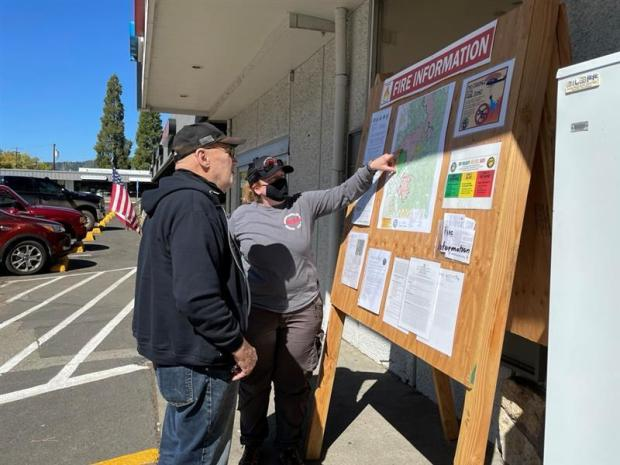 a public information officer shares fire information at a store in Canyonville