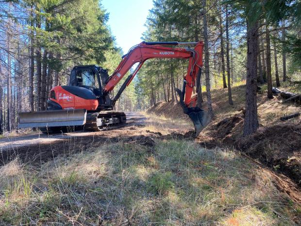 an excavator opens a ditch after firefighting effort