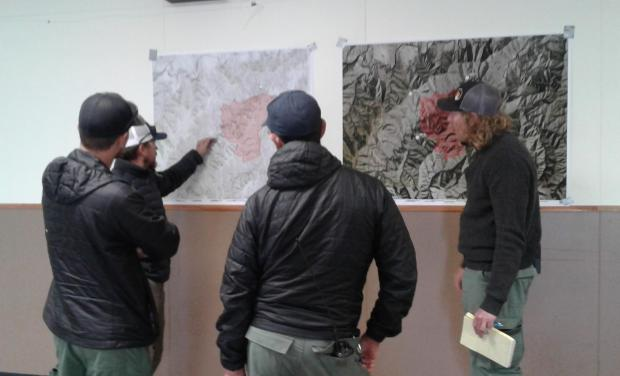 Baker River Hotshots discuss strategies for battling the Joseph Canyon Fire before heading out to the line this morning. Photo by Sara Bethscheider, WWNF