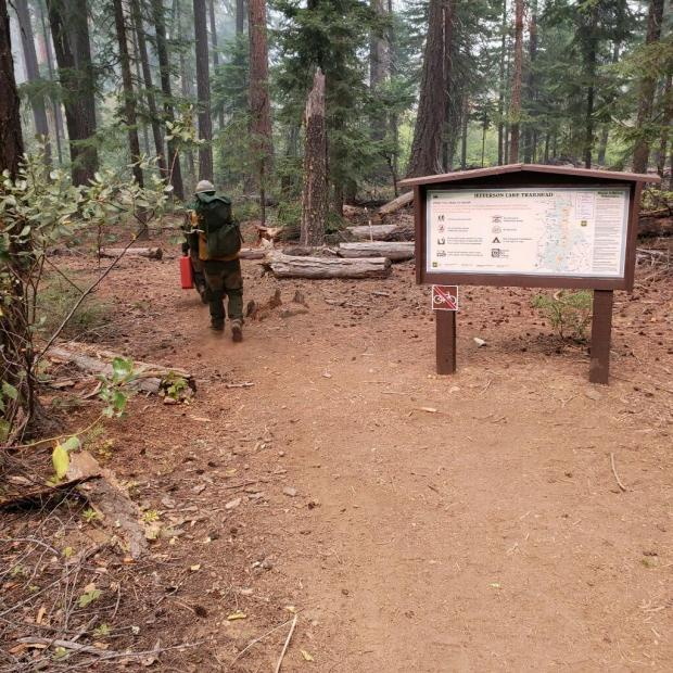 Firefighters walking past the trailhead sign