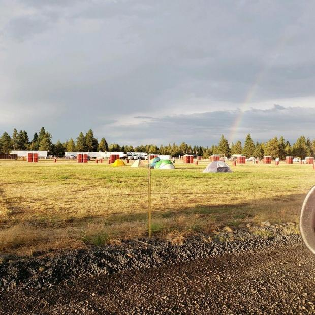 Tents are in the field at camp, and there is a rainbow overhead.