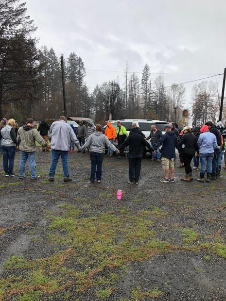 Residents gather in a circle for a prayer together.