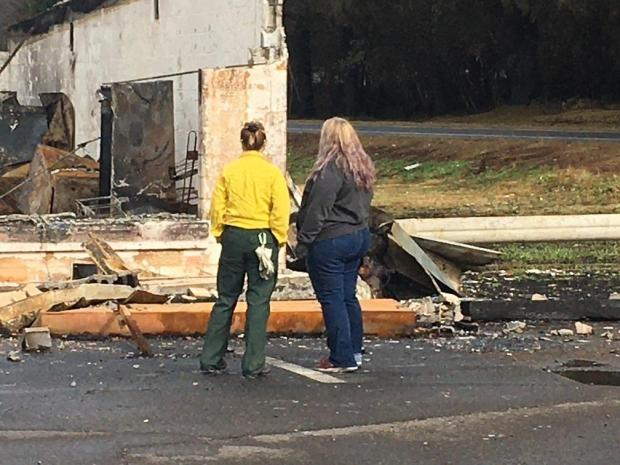 Public Information Officer and resident look at a fallen building together.