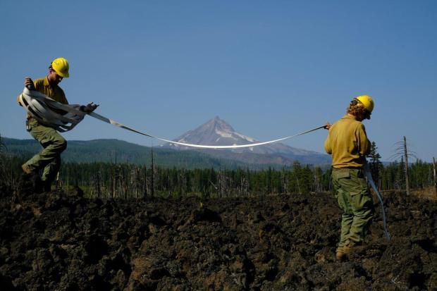 Div R Backhaul 03: Kegan Allen, left, and Nick Burns of the Metolius WFM butterfly hose on the Jefferson Lake Lava Flow during a backhaul mission in Division Romeo on October 2, 2020.