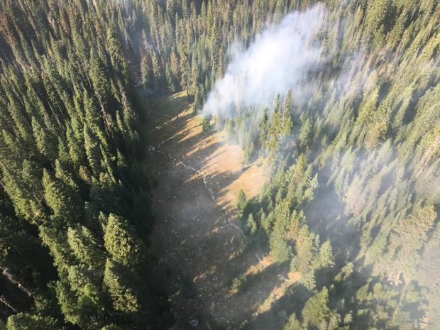 An existing spot fire spread to 2 acres, moving out of the Mina River riparian area and into an avalanche chute
