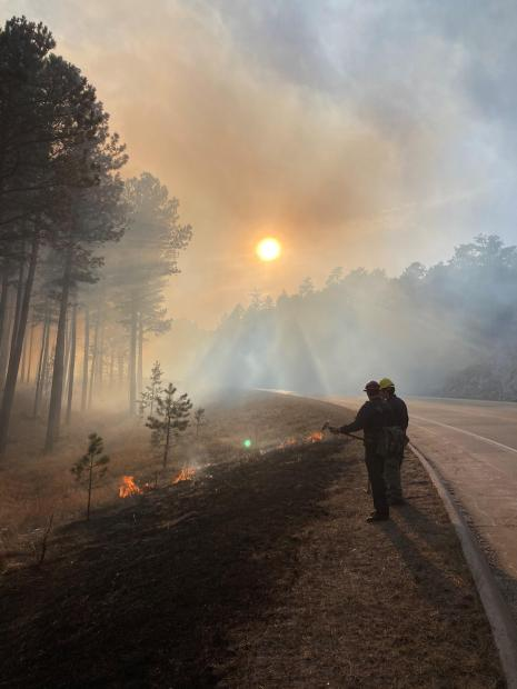 Firefighers watch the edge of the fireline next to the highway