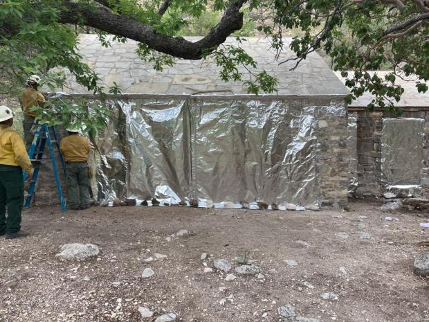Wrapping shed side of Pratt Cabin with fire resistive material