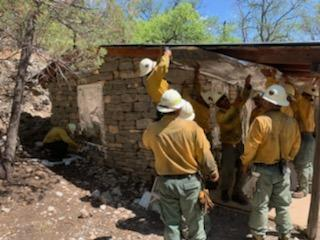 Firefighters wrapping Hunter Line Shack with fire resistive material
