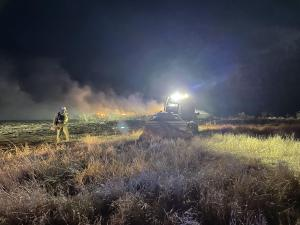 A dozer works to improve containment lines along the west flank of the fire. Hay bales can be seen burning in the background